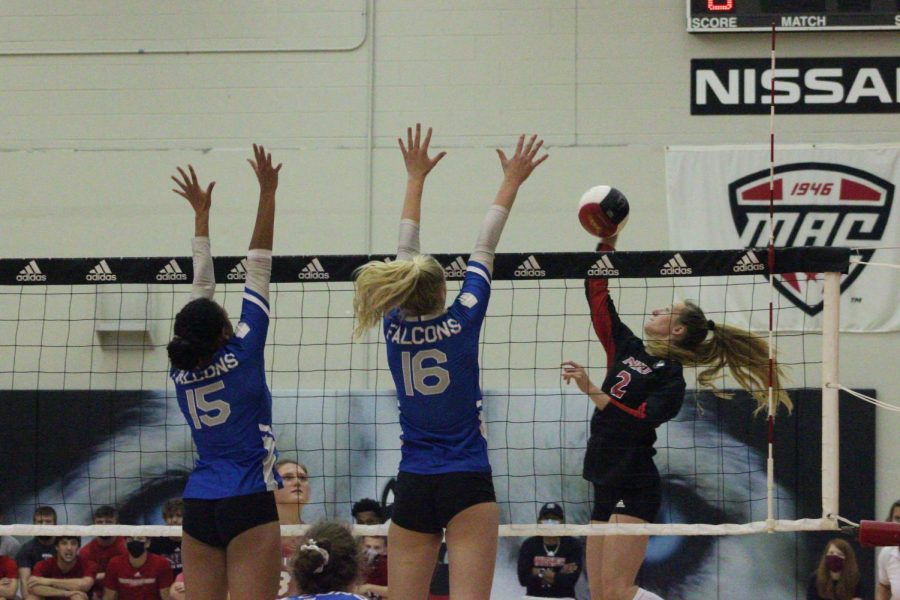 Junior outside hitter Katie Jablonski (right) attempts to spike the ball over a a wall of Air Force players in the Huskies 3-0 win at Victor E. Court on Aug. 28.