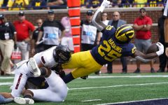 Michigan running back Hassan Haskins (25) dives into the end zone for a five-yard touchdown run against Northern Illinois in the first half of a NCAA college football game in Ann Arbor, Mich., Saturday, Sept. 18, 2021.
