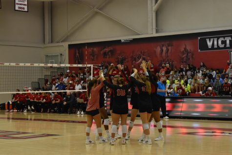 The volleyball team huddles during the first set of their matchup on Sept. 18 against Wisconsin. The loss to the Badgers drops NIU to 6-4.