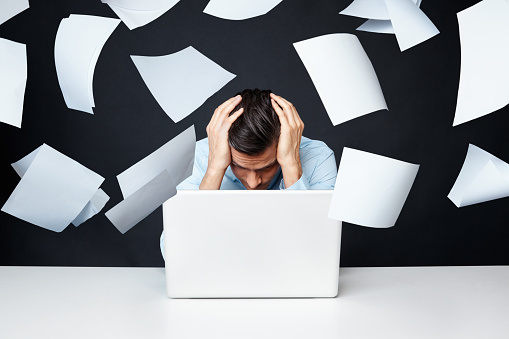 Stressed man sitting by laptop while papers fall over him.