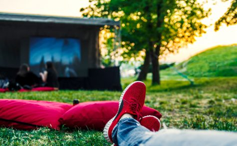 Person watches movie in open cinema in green nature.