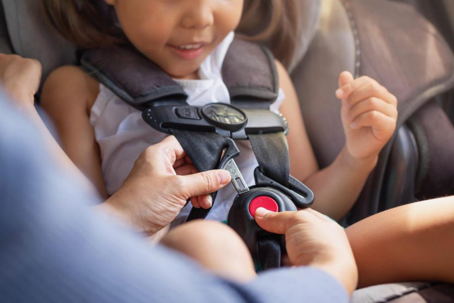 Parent buckling her childs seat belt in the car.