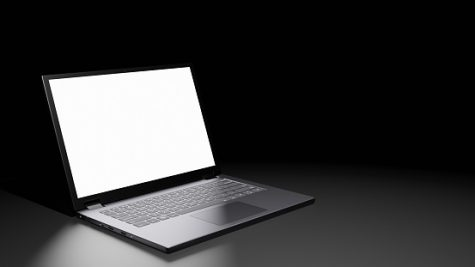 Opened laptop with blank screen display on the floor in a dark room.