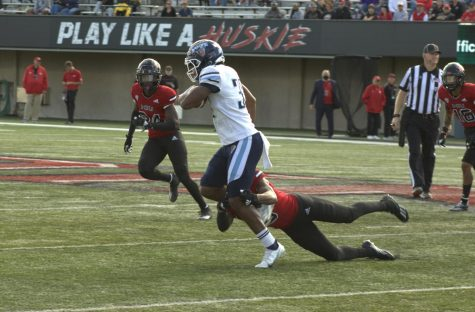 Maine senior running back Jordan Rowell tries to evade an NIU tackle late at Huskie Stadium on Sept. 25. Rowell, the native of Elmhurst, had two carries for five yards in his return to Huskie Stadium.