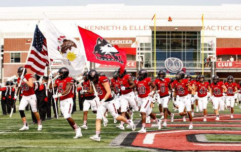 The NIU football team runs onto the field at Huskie Stadium ahead of their game Sept. 11 against Wyoming.