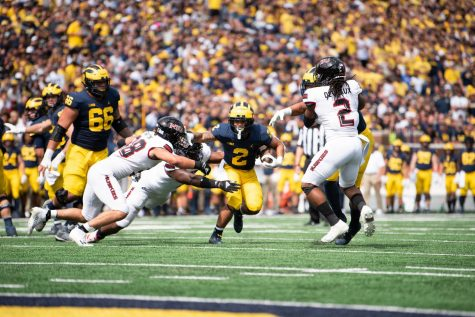 NIU linebackers, sophomore Nick Rattin (left) and redshirt senior Lance Deveaux (right) try and tackle Michigan sophomore running back Blake Corum (middle). Corum led the Wolverines with 125 yards rushing in a 63-10 win over the Huskies on Sept. 18.