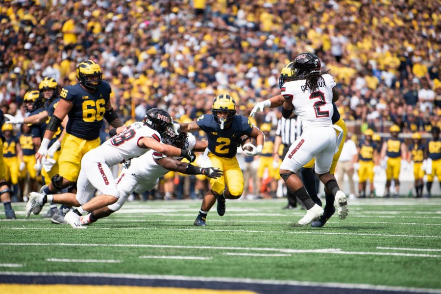 NIU+linebackers%2C+sophomore+Nick+Rattin+%28left%29+and+redshirt+senior+Lance+Deveaux+%28right%29+try+and+tackle+Michigan+sophomore+running+back+Blake+Corum+%28middle%29.+Corum+led+the+Wolverines+with+125+yards+rushing+in+a+63-10+win+over+the+Huskies+on+Sept.+18.