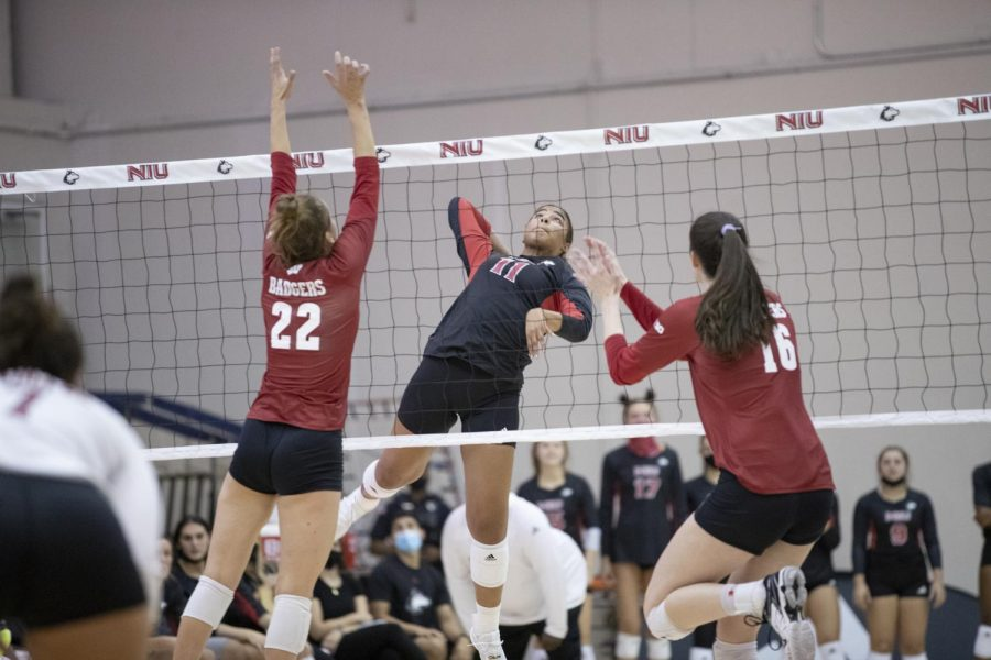 Freshman middle blocker Charli Atiemo (middle) leaps to perform a spike against Wisconsin on Sept. 18 at Victor E. Court.