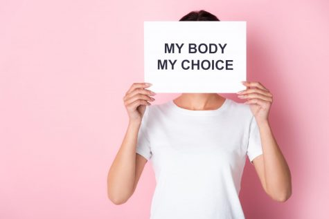 A person holding a sign, advocating for reproductive rights.