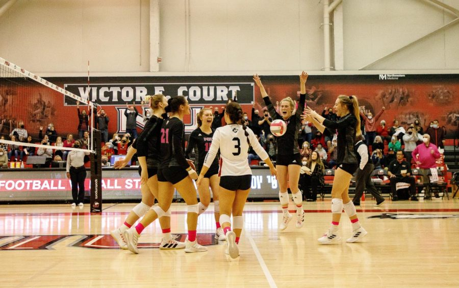The volleyball team celebrates after scoring a point against Toledo on Oct. 22. NIU defeated the Rockets 3-1 at Victor E. Court.