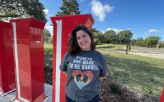 Amanda McGovern, a junior communicative disorders major stands in front of an NIU sign wearing a shirt that says kidneys are meant to be shared.