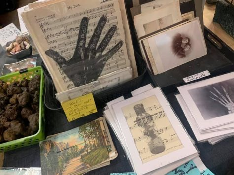 A vendor table displays horror antique art items for sale at the 2019 Dark Art and Oddities convention.