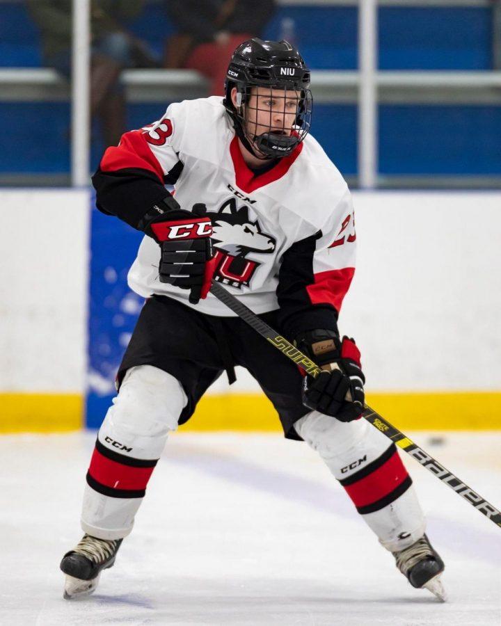 Junior forward Rodahn Evans plays the puck in an NIU Division I hockey game.