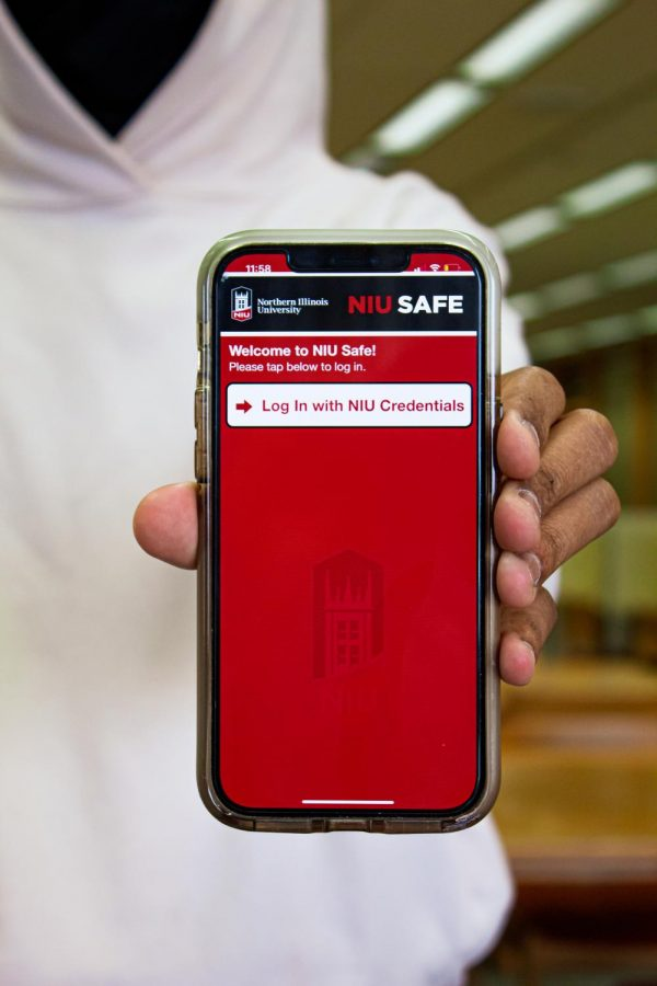 A+student+holding+a+phone+with+the+NIU+Safe+App.+